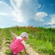 Baby on a lane amongst a field — Stockfoto