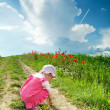 Baby on a lane amongst a field — Stock fotografie