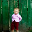 Baby-girl near green fence — Stock Photo