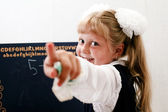 Little girl near chalkboard — Foto Stock
