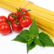 Pasta and fresh red tomatoes on white background — Stock Photo