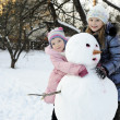 Happy sisters posing with snowman — Stock Photo