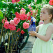 Little girl watering flowers in a greenhouse — Stock Photo #9362616