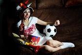 Girl on a sofa watching football on TV — Stock Photo