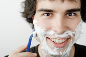 A young handsome man shaving — Stock Photo