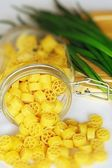 Bright yellow pasta in a jar and onions — Stock Photo