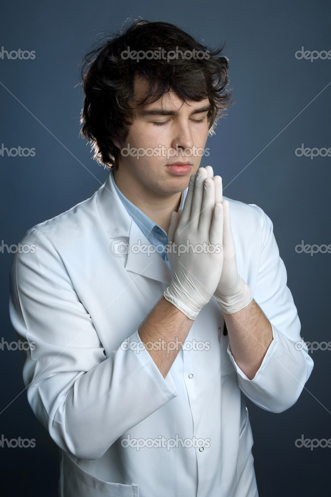 An image of a young doctor in gloves praying — Stock Photo #9362867
