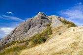 Dağ tepe mavi gökyüzü altında. — Stok fotoğraf