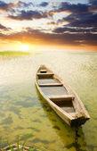 Asunset に対して海岸でボートします。. — ストック写真