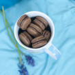 French macarons (macaron) in the cup and blue flowers - Stock Photo