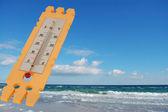 Mavi gökyüzü arka plan üzerinde termometre — Stok fotoğraf