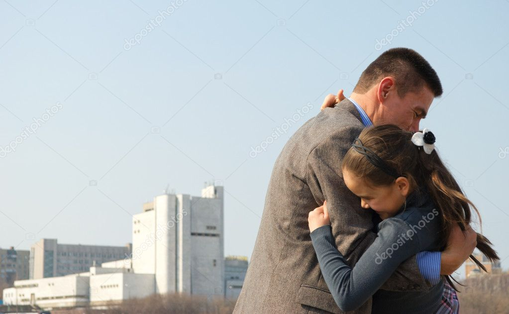Joyful father hugs his daughter, against the backdrop of the city.  Stock Photo #10456392