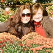 Two sisters full of autumn flowers — Stock Photo