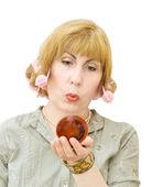 Blonďatá žena s natáčky na vlasy při pohledu do zrcadla — Stock fotografie