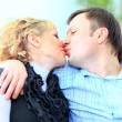 Portrait of an affectionate man kissing his wife sitting on bed at home — Stock Photo