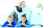 Usmívající se děti hledají představuje vánoční boty a rodina na pohovce — Stock fotografie