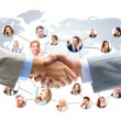 Business handshake with company team in background — Stock Photo