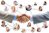 Apretón de manos de negocio con equipo de fondo — Foto de Stock