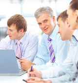 Happy business team talking together during a meeting sitting at — Zdjęcie stockowe