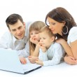 Loving family looking at a laptop lying down on bed at home — Stock Photo
