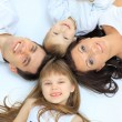 Happy family, mother, father and daughter resting on the white bed — Stock Photo #9262522
