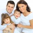 Portrait of happy family smiling at the camera — Stock Photo