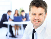 Confident young business man attending a meeting with his colleagues — Stock Photo