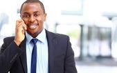 Biznesmen uśmiechający się na ten telefon w jego biurze — Zdjęcie stockowe