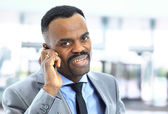 Attractive smiling Afro-American young businessman on phone in office — Stock Photo