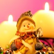 Stock Photo: Snowman Figurine and Burning Candles on Romantic Pink Background