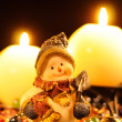 Snowman Figurine and Burning Candles — Stock Photo #8047042