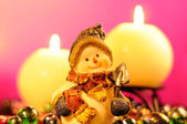 Snowman Figurine and Burning Candles on Romantic Pink Background — Stock Photo