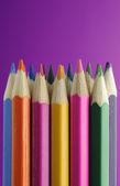 Kolorowe kredki na fioletowym tle — Zdjęcie stockowe