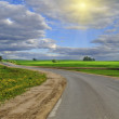 Stock Photo: Empty Road and Sun Breaking Through Clouds