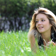 Blonde lying on grass field at the park — Stok fotoğraf