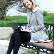 Girl using laptop while sitting on bench at spring park — Stock Photo #10503581