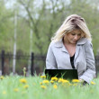 Girl using laptop while sitting on bench at spring park — Stock Photo