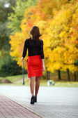 Walking woman red skirt — Stock Photo