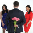 Man with a bouquet of flowers and two young women — Stockfoto