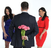 Man with a bouquet of flowers and two young women — Stock Photo