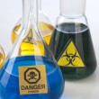 Glass laboratory equipment with symbol biohazard and danger — Stock Photo