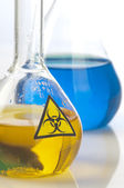 Glass laboratory equipment with symbol biohazard — Stock Photo