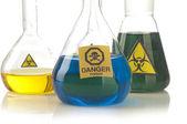 Glass laboratory equipment with symbol biohazard and danger — Stock Photo