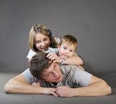 Heureux, heureux jeune famille dans une joyeuse huddle — Photo