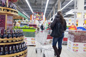 Young woman shopping at supermarket — Stockfoto