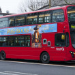 Stock Photo: Double Decker red bus rides on street in London