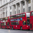 Double Decker red bus  rides on the street in  London - Stock Photo