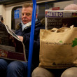 In London Underground train reading the morning newspaper — Stock Photo