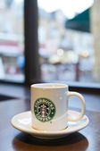 Starbucks cup of coffee in coffeehouse — Stock Photo