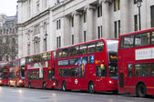 Double Decker red bus rides on the street in London — Stok fotoğraf
